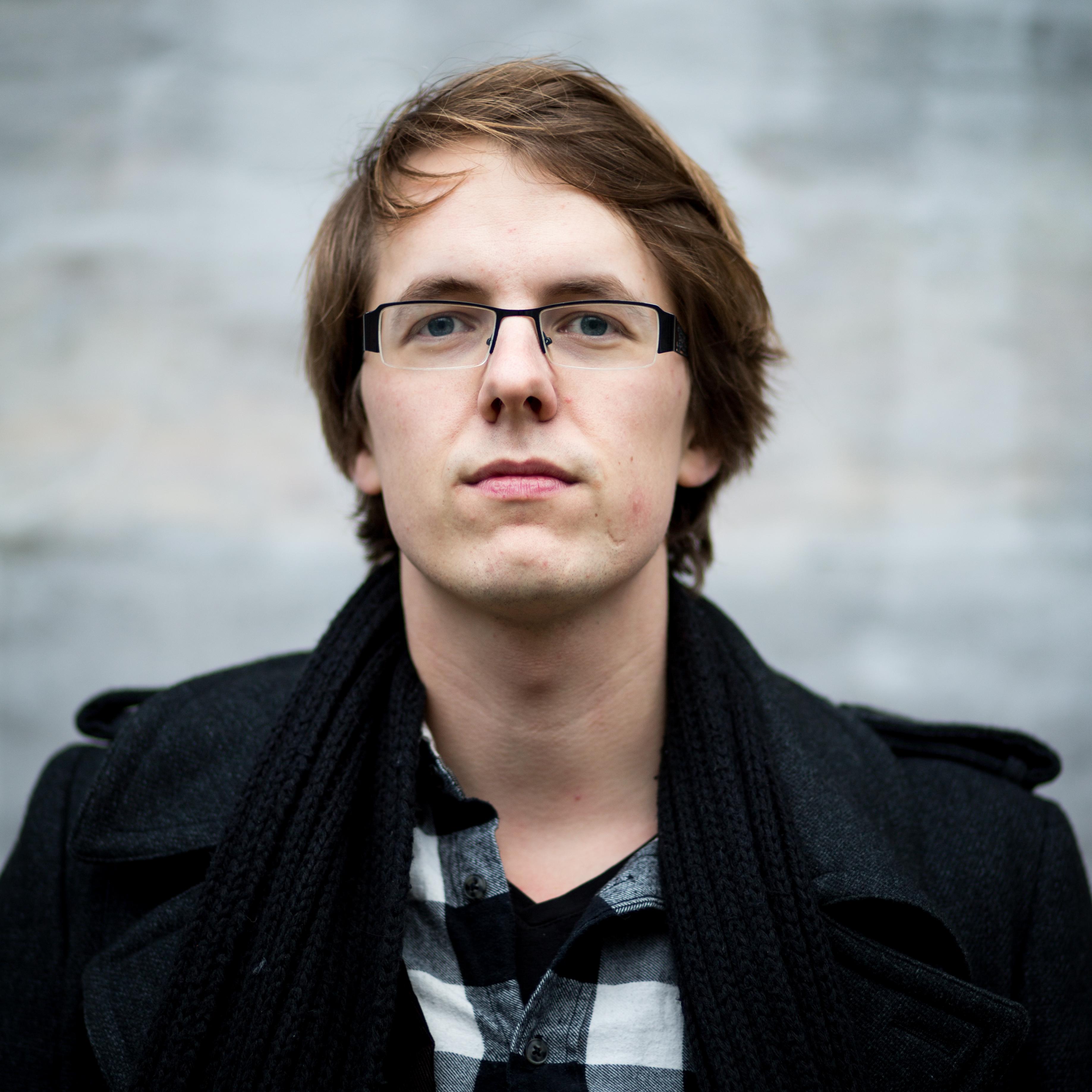 Foto van Maarten Boudry die buiten staat en voor zich uit kijkt, richting de kijker.