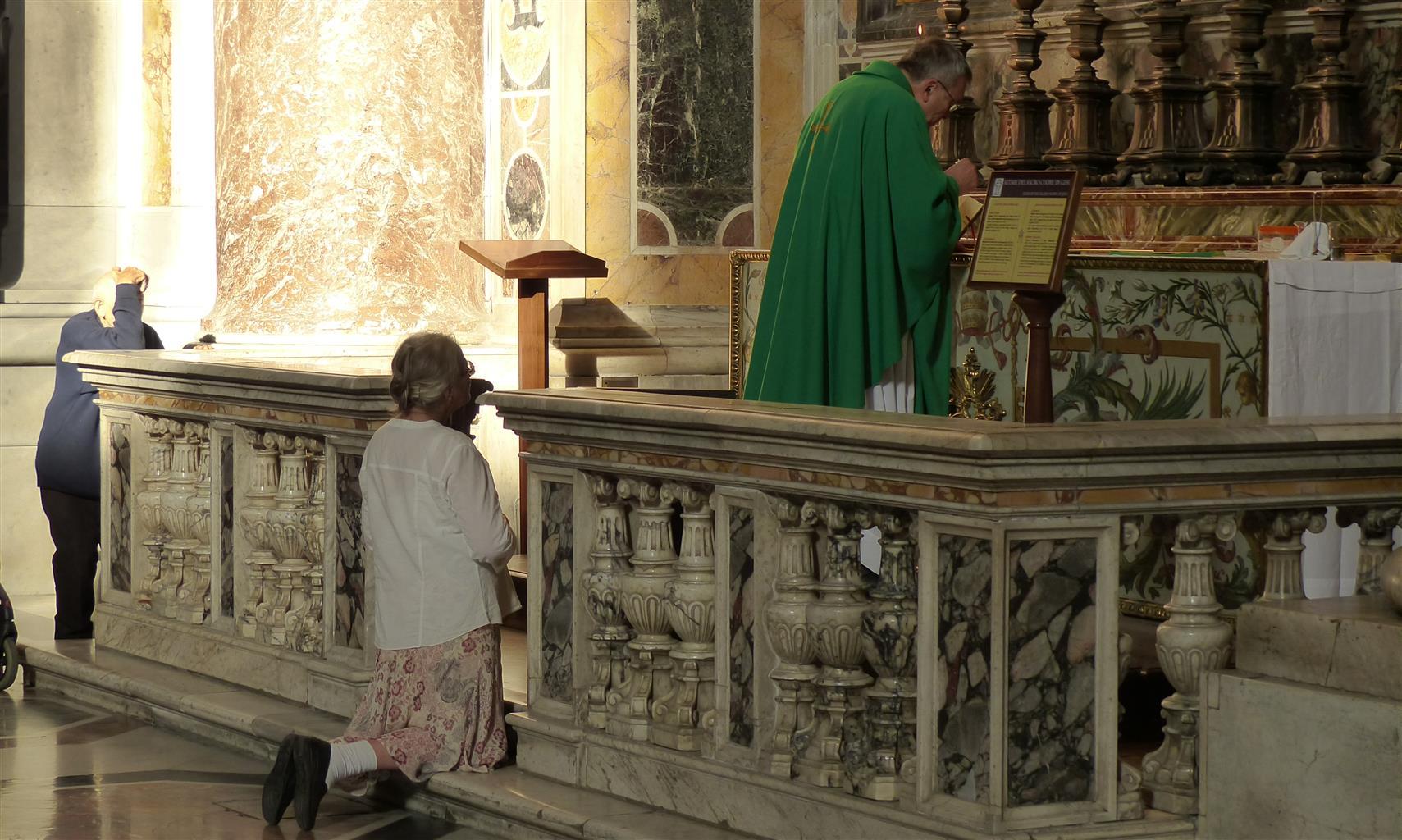 Een vropuwtje komt om een sacrament in een bijkapel in de Sint Pietersbasiliek in Rome.