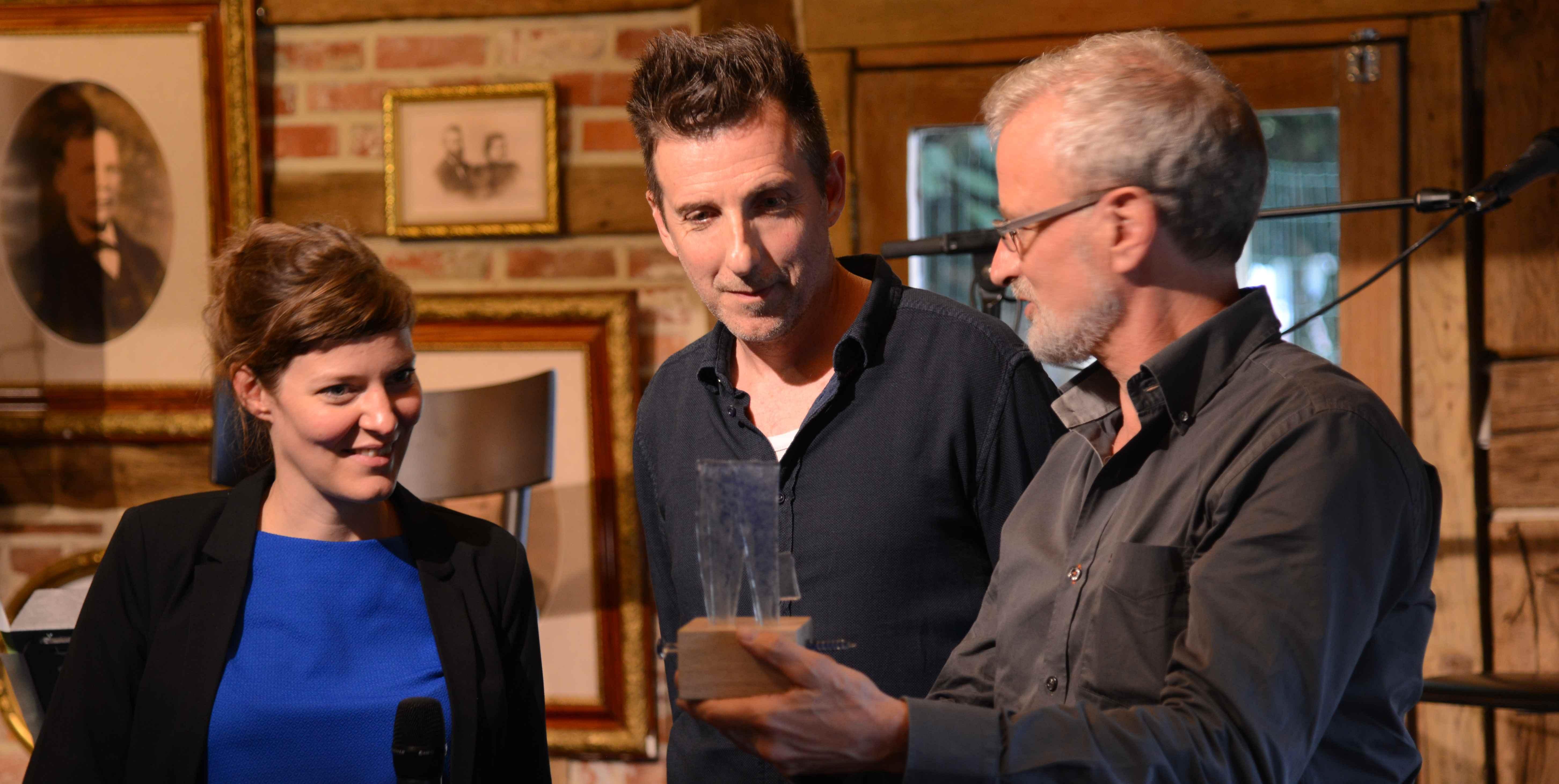 Paul De Belder geeft de PDW-trofee aan Maxie Eckert en Mark Eeckhaut